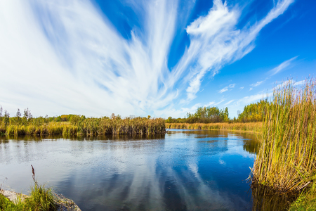 cirrus: Indian summer in Canada. Magic reflection. Cirrus clouds are reflected in the Winnipeg River, Old Pinawa Dam Park. The concept of ecological tourism
