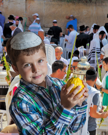 jewish: Charming seven year old boy in white festive skullcap with etrog. Sukkot at the Western Wall of Temple in Jerusalem