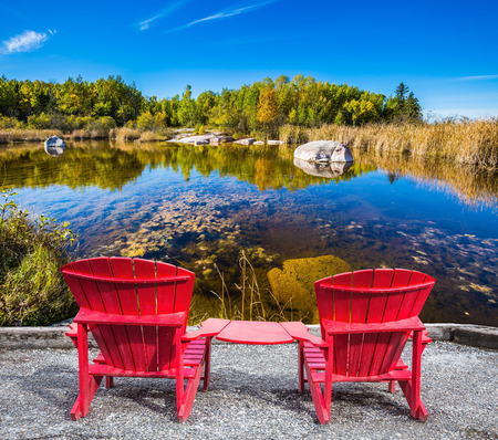 Lovely place. Two red beach chairs on the riverbank. Cirrus clouds are reflected in the Winnipeg River. Old Pinawa Dam Park. The concept of ecological and recreational tourism