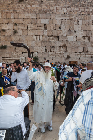 JERUSALEM, ISRAEL - OCTOBER 12, 2014: . Elderly religious Jew with a Shofar. Morning autumn Sukkot. The area in front of Western Wall of  Temple filled with people Editorial