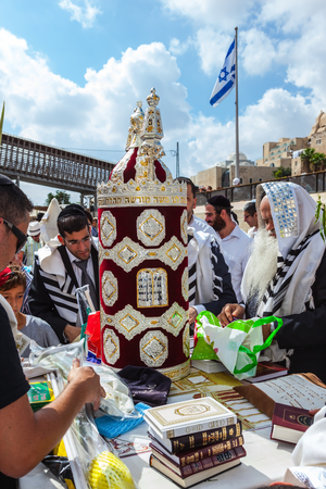 JERUSALEM, ISRAEL - OCTOBER 12, 2014: Morning autumn Sukkot. The area in front of Western Wall of  Temple. Crowd of Jewish worshipers in white wearing prayer shawls. On table there is Torah Roll in magnificent case