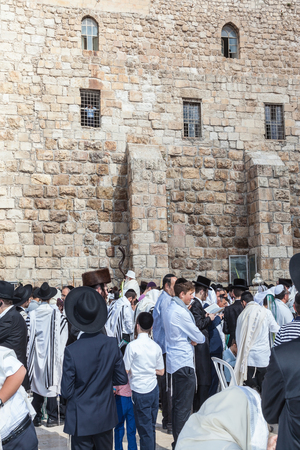 JERUSALEM, ISRAEL - OCTOBER 12, 2014: Crowd of faithful Jews wearing prayer shawls. Morning autumn Sukkot. The area in front of Western Wall of  Temple filled with people Editorial