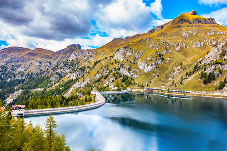 smooth: Autumn day. The clouds are reflected in the smooth cold water. Grandiose glacial lake Lago di Fedaia in the Dolomites. The concept of ecological and extreme tourism Stock Photo