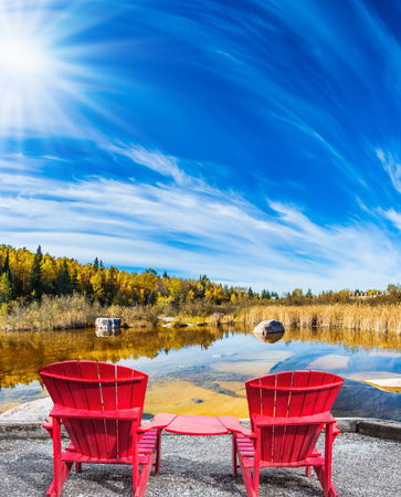 Lovely place to relax. Two red beach chairs on the riverbank. Cirrus clouds are reflected in the Winnipeg River. Old Pinawa Dam Park. The concept of ecological and recreational tourism