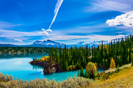 abraham: Turquoise Abraham Lake. In the blue sky silver trace of the plane. Rocky Mountains of Canada in the Indian summer. The concept of ecological and active tourism