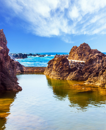 smooth: Volcanic island of Madeira. Small bay with smooth water on beautiful coast. Rocks and grottoes of the Atlantic coast. The concept of exotic and ecological tourism