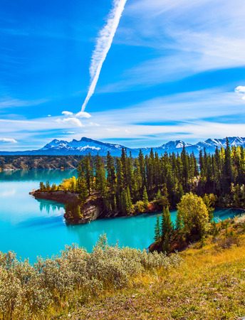 Rocky Mountains of Canada in the Indian summer. In the blue sky silver trace of the plane. Magnificent turquoise Abraham Lake. The concept of ecological and active tourism Stock Photo
