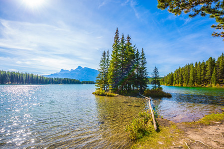 Lake Two Jack in the Rocky Mountains. The morning sun warms the lake and a small island. Golden Autumn in Canada. The concept of ecological and active touris
