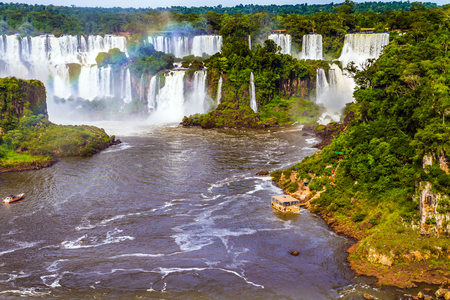Boiling water creates a watery dust and a rainbow. Several waterfalls from 275 Iguazu Falls. The concept of exotic and extreme tourism