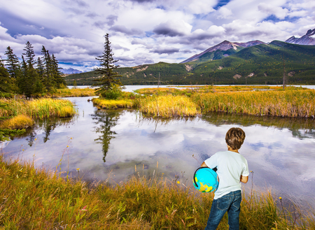 national geographic: Trip to the Indian summer. Handsome boy with a globe in the Rocky Mountains. The concept of ecological and active tourism