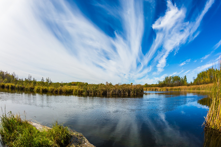 cirrus: Wonderful clouds day. Magic reflection. Cirrus clouds are reflected in the Winnipeg River, Old Pinawa Dam Park. The concept of ecological and recreational tourism Stock Photo