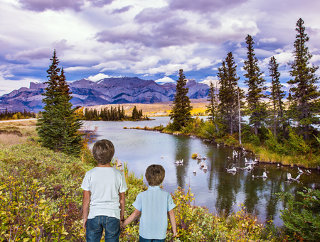 national geographic: Two lovely boys admire the mountains and lakes. Magnificent landscape in the Rocky Mountains. The concept of ecological and active tourism
