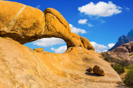 Stone arch of Spitzkoppe. Concept of extreme and ecological tourism. Natural group of smooth bald granites among the Namib Desert, Namibia