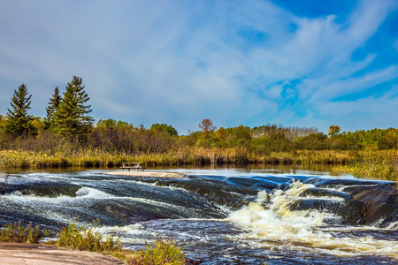 The concept of travel Around the World. Old Pinawa Dam Park. Magnificent rapids on smooth stones of the Winnipeg River. Yellowed autumn grass on banks of the river Stock Photo