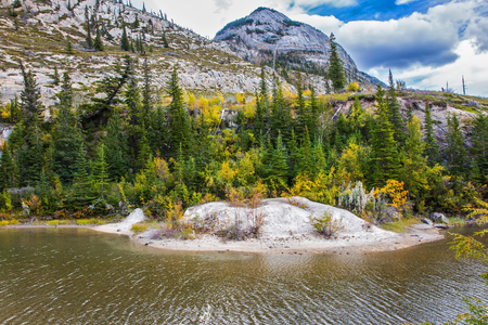 Concept of active automobile and ecological tourism. Rocks, lakes and yellow grass under flying clouds. Impressive trip to the Rockies of Canada Stock Photo
