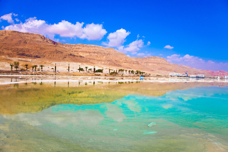 turismo ecologico: Midday heat evaporates water of the Dead Sea, Israel. Between the sea and dry mountains of red sandstone highway passes. The concept of medical and ecological tourism