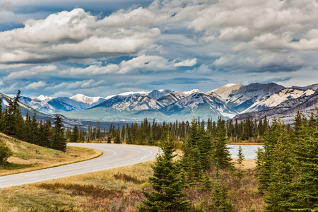 The road to distant snow-capped mountains. Indian summer in the Rockies of Canada. Rocks and lakes under flying clouds. Concept of active and ecological tourism