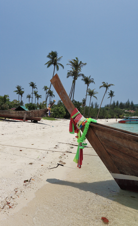 Boat Longtail decorated with silk tapes expects tourists. Island Phi-Phi, Thailand