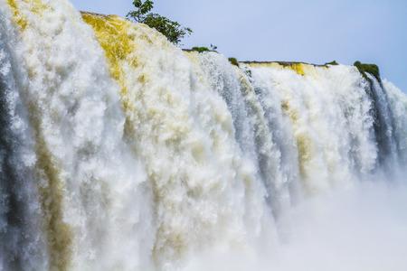 流れ落ちる水の世界をゴロゴロします。3 つの国の国境の南アメリカのイグアスの滝。アクティブな観光の概念