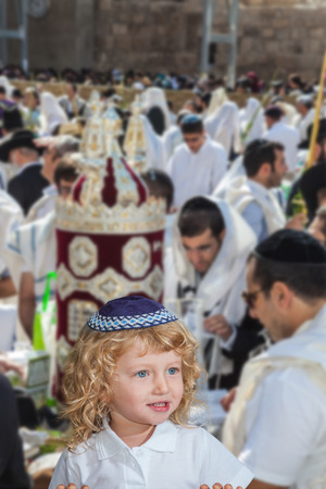 sukkoth festival: Handsome little boy with blond side curls and blue eyes, in skullcap. Autumn Jewish holiday Sukkot.  Western Wall of the Temple. Jerusalem, Israel