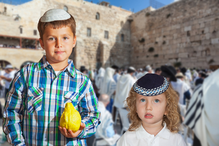 Autumn Jewish holiday Sukkot. Two beautiful boys in yarmulks with citruse in hands. The greatest shrine of Judaism is the Western Wall of the Temple. Jerusalem, Israel