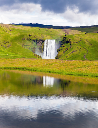 Abounding waterfall Skogafoss reflected in small pond near the road. An incredible reflection Stock Photo