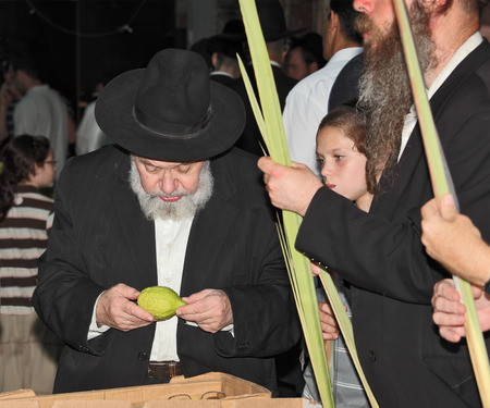 bene: BENE - BERAK, ISRAEL - SEPTEMBER 17, 2013:  The elderly man with gray-haired beard chooses a citrus.  Big market on the eve of the Jewish holiday of Sukkot