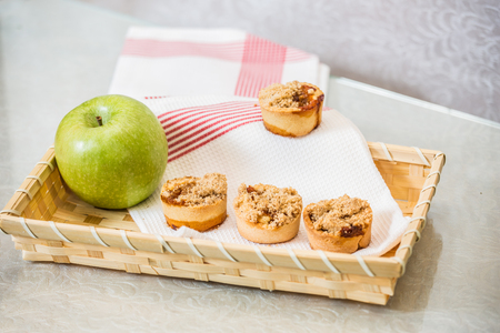 Magnificent portioned tartlet cakes with sweet stuffing. Professional baking. Background of wicker basket, white dish towel and green apple Stock fotó