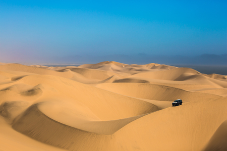 Dangerous jeep - safari through the huge sand dunes on the ocean shore. Atlantic coast of Namibia, south of Africa. The concept of exotic and extreme travel