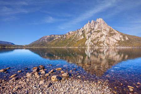 Picturesque mountain in San Carlos de Bariloche, Argentina. The water of shallow lake reflects sharp rocks. The concept of exotic and extreme tourism Stock Photo