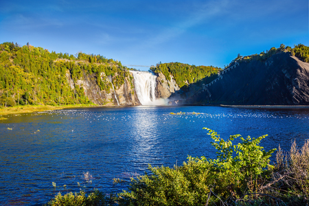 Sunny autumn day. The vast blue lake and powerful waterfall Montmorency in Montmorency Falls Park, in vicinities Quebec. The concept of active and cultural tourism