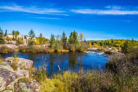 Thin cirrus clouds and foam on the Winnipeg River. Tranquil landscape in the Old Pinawa Dam Park. Trend of travel Around the World