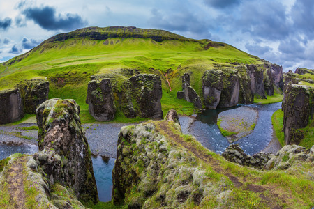Steep vertical cliffs surround the stream of very cold water. The most beautiful canyon in Iceland - Fyadrarglyufur Stock Photo