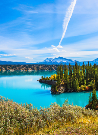 Magnificent turquoise Abraham Lake. In the blue sky silver trace of the plane. Rocky Mountains of Canada in the Indian summer. The concept of ecological and active tourism Stock Photo