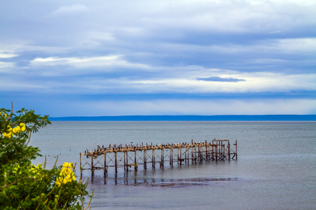 The legendary Strait of Magellan. Cloudy morning. South of South America. Rusted and destroyed remains of the sea mooring. The concept of extreme and active tourism Stock Photo
