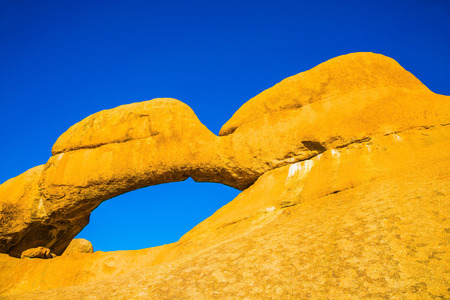 Stone arch of Spitzkoppe. Natural group of smooth bald granites among the Namib Desert, Namibia. Concept of extreme and ecological tourism Stock Photo