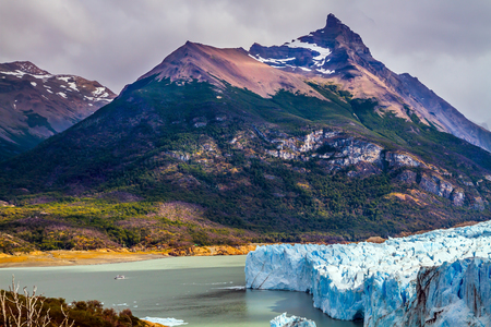 The fantastic glacier Perito Moreno, in the lake Argentine, Patagonia. Clouds and glacier shine with reflected sunlight. The concept of exotic and extreme tourism Stock Photo