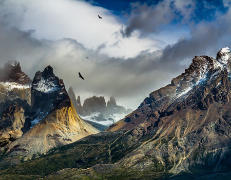 National Park Torres del Paine, Chile. Black cliffs of Los Kuernos. Hurricane wind blows cold clouds. The concept of active and extreme tourism