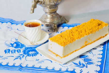 Exquisite white cheesecake, sprinkled with sweet orange crumbs. Professional bakery. The background is samovar and porcelain white cup with hot tea on blue kitchen towel