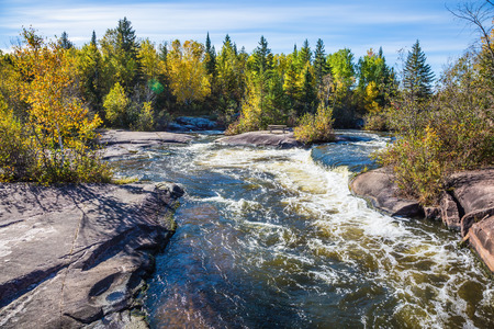 Old Pinawa Dam Provincial Heritage Park. Warm autumn day. Foam water rapids on the smooth stones of the Winnipeg River. The concept of ecological and adventure tourism