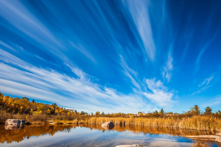 Cirrus clouds are reflected in the Winnipeg River. Wonderful autumn day. Old Pinawa Dam Park. The concept of ecological and recreational tourism Stock Photo