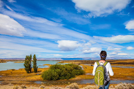Woman with a backpack is standing in the Patagonian pampas. The concept of active and ecological tourism Stock Photo
