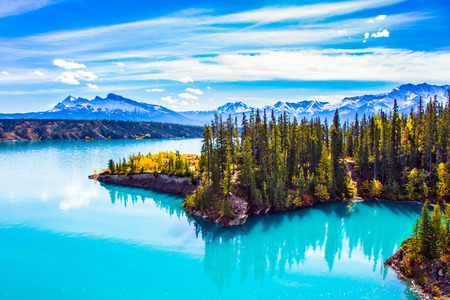 Abraham Lake is in the Rockies of Canada. Turquoise smooth water reflects the sky. Warm sunny day in Indian summer. The concept of ecological and active tourism Standard-Bild