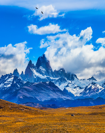 The concept of active and extreme tourism. Argentine. Desert and mountains. The famous ridge Mount Fitz Roy in the clouds and the Patagonian prairie Stock Photo