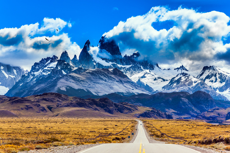 Argentine Patagonia. Summer day in February. Fine highway to the majestic Mount Fitz Roy. The concept of active and extreme tourism. The Andean condors hover over the prairie