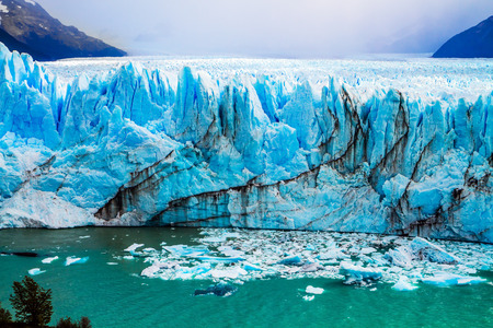 The colossal Glacier Perito Moreno in Patagonia on Lake Argentino. The cloudy sky covers the horizon. The concept of active and ecological tourism