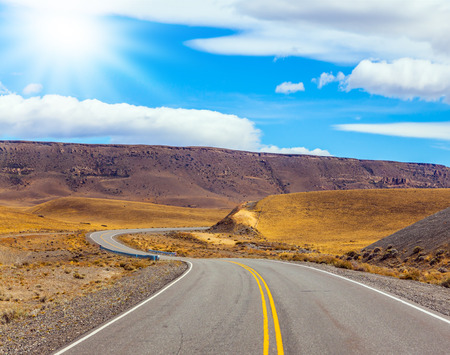 Asphalt road in the Argentine prairie. Patagonia. Summer day in February. The concept of active and extreme tourism. The summer sun illuminates the prairie