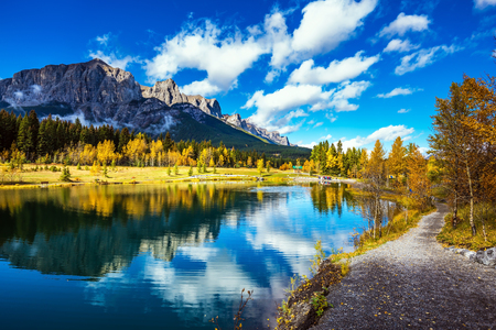 The path and yellowing aspens surround the lake. The concept of hiking. Canmore, near Banff National Park