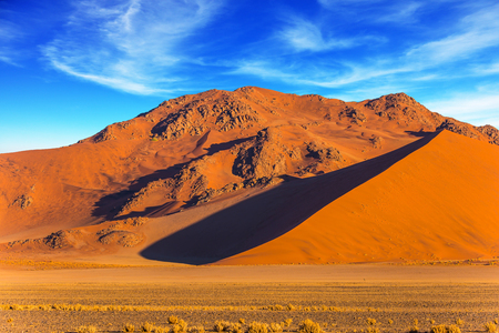 Orang and yellow dunes of the Namib desert. The concept of extreme and exotic tourism. Namibia, South Africa. Sunset in the desert Stock Photo