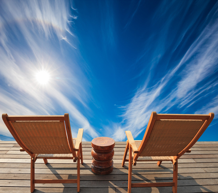 turismo ecologico:  Lovely place to relax. Two deck chairs on a wooden platform. Cirrus clouds in the autumn sky.  The concept of recreational tourism